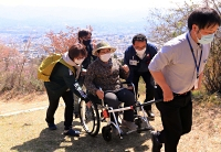 介助を受けて車椅子で坂道を上る女性(中央)