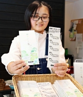 蚕のイラストをあしらったメモ帳(左)とシールを持つ福沢さん