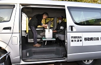 移動投票車で1票を投じる有権者(左)=21日午後5時12分、筑北村坂井