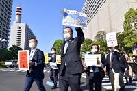 入管難民法改正案の廃案を求め、プラカードを掲げて歩く出井弁護士(中央)ら=21日、東京・霞が関