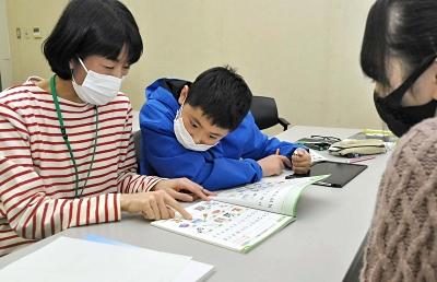 ヤングにほんご教室でボランティアと学ぶ生徒(中央)