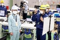 高浜原発1、2号機を視察し、関西電力の担当者から説明を受ける福井県の杉本達治知事(手前左)=24日午前、福井県高浜町