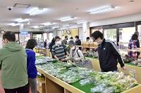 道の駅信州新町で、山菜などを品定めする買い物客