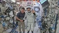 日本時間2日、米宇宙船クルードラゴン1号機の搭乗前に、国際宇宙ステーションで手を振る野口聡一さん(右)。左は星出彰彦さん(JAXA提供・共同)
