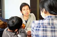 松本市の自宅でくつろぐ盛田大介さん(中央)家族。おやつをおいしそうに食べる長男の姿にほほ笑む