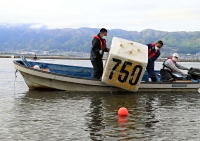 イタリア代表が事前キャンプを打診している漕艇場。7日は、翌日に開幕する「信毎諏訪湖レガッタ」に向け県ボート協会員らが準備を進めた=7日午前6時36分、下諏訪町