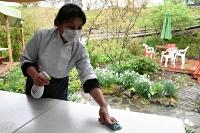 感染対策で設けた屋外テラス席を消毒するイタリア料理店「梅蔵」の高良さん=7日、茅野市豊平