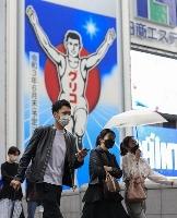 大阪・ミナミを歩くマスク姿の人たち=7日夕