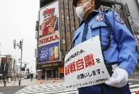 5日に札幌市で行われた五輪マラソンのテスト大会で、沿道での観戦自粛呼び掛けの案内を掲げる警備員=ススキノ交差点