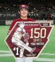 通算150セーブを達成し、記念のボードを手にする楽天・松井=札幌ドーム