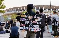 陸上のテスト大会が行われている国立競技場周辺で、東京五輪中止を訴える人たち=9日午後、東京都新宿区