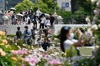 大阪・中之島公園を散策するマスク姿の人たち=9日午後