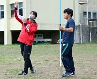 陸上部顧問を務める茅野高校で、部員にやり投げの指導をする柄沢さん(左)=4月28日、茅野市
