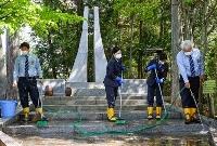 信楽鉄道事故の慰霊碑を清掃する人たち=10日午前、滋賀県甲賀市