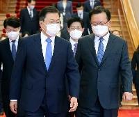 14日、ソウルの韓国大統領府で金富謙首相(右)と並んで歩く文在寅大統領(聯合=共同)