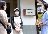 被災した自宅を改修したパン店の前で客と談笑する天利さん(中央)