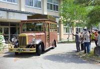 関係者に見送られて出発するボンネットバス