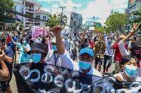 国軍に対する抗議のデモ行進をする人々=12日、ミャンマー・ヤンゴン(AP=共同)