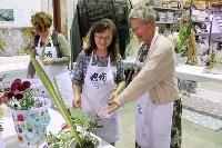 15日、オーストラリア・サンシャインコーストで田中弘美さん(中央)に助言を求めながら花を生ける参加者(共同)