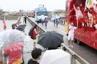 中国地方最長の河川・江の川に架かる江川橋でポーズする聖火ランナー=15日午後、島根県江津市