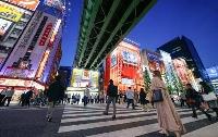 東京・秋葉原の横断歩道を行き交うマスク姿の人たち=15日夜