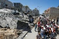 15日、パレスチナ自治区ガザで、イスラエルの空爆により破壊された建物横で、死亡したパレスチナ人を悼む住民(ロイター=共同)