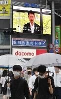 感染対策を呼び掛ける湯崎英彦広島県知事の映像が流れる大型ビジョン=15日午後、広島市