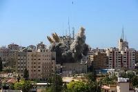 15日、パレスチナ自治区ガザで、ミサイルを受け煙が立ち上るビル。AP通信やアルジャジーラが入居している(ロイター=共同)