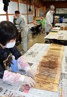 丁寧に経典を広げ、傷みを確認するボランティアら=14日、長野市立博物館