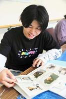 洗浄した写真を見る鈴木さん
