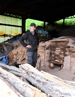 炭焼き窯の前に立つ桜田さん。「竹炭を入れてご飯を炊くとおいしいぞ」