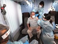 大型バスを利用した集団接種会場で新型コロナワクチンの接種を受ける男性=31日午後3時34分、千曲市の八幡公民館