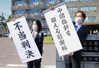 東電福島第1原発避難者訴訟で、国への請求を棄却した判決を受け「不当判決」の幕を掲げる弁護士ら=2日午後、新潟地裁前