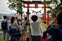 生島足島神社で東鳥居越しの太陽を写真に収める人たち