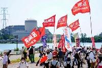 関西電力美浜原発3号機(左奥)の再稼働に抗議する人たち=23日午後、福井県美浜町