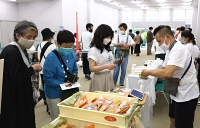 パンや弁当など自慢の品を並べて来場者を迎える地元の自営業者(右)ら=松本市