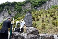 崩落した大西山(正面)の下で犠牲者を悼む参列者=29日