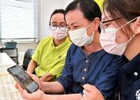 モンゴル人の同僚に息子の写真を見せる介護技能実習生のビャンバスレンさん(右から2人目)=2021年6月11日、長野市