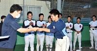 部員が見守る中、宮下主将に背番号を手渡す熊谷監督(左)