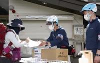 登山者(左)に紙を渡す御嶽山火山マイスター