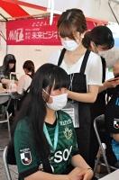 山雅サポーター(手前)のヘアアレンジをする専門学校生