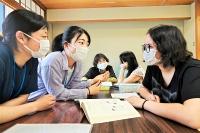 日本語教室で日系ブラジル人の奥間さん(右)と話す高校生ボランティアの井村さん(左)と小林さん=2021年6月5日、安曇野市の穂高公民館