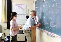 互いに黒板を使い意思疎通を図るベトナム人技能実習生のフォンさん(左)と林さん=2021年6月20日、飯田市の龍江公民館