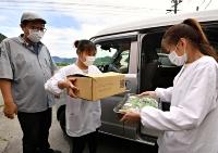 納品に出掛けるベトナム人技能実習生の(右から)アンさん、ティンさんと、見送る東久保社長=2021年6月29日、長和町