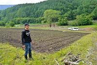 被災した農地に立ち「2季ぶりに作付けできる」と喜ぶ昌則さん