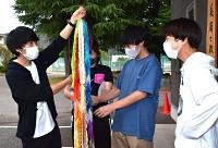 松本県ケ丘高生(右)から千羽鶴を受け取った松本美須々ケ丘高の3人