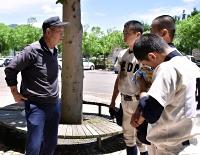 「打てないときはスクイズなど攻め方を変えないと」。相沢さん(左)の指導は試合後も続いた=7日