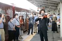 上田駅ホームで演奏する大迫さん(右)と演奏を聴く乗客ら