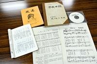 小林さんが疎開先の坂の上小学校に贈った楽譜(右下)。CD、訪問記録が残る学校日誌、文集も同校に保管されていた