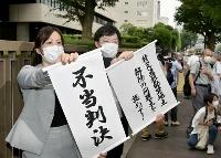 判決を受け、東京地裁前で「不当判決」と書かれた垂れ幕を掲げる原告側弁護士=12日午後